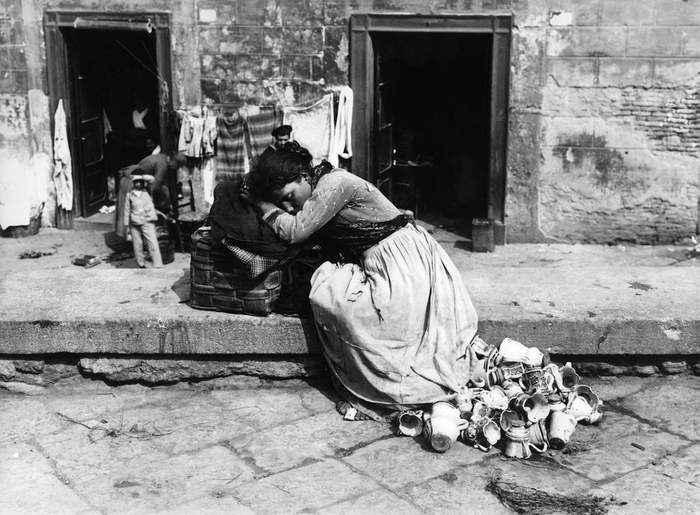 Una ragazza che vende tazzine e altri oggetti di ceramica si riposa in una strada di Napoli, verso il 1885. (ANSA ALINARI)